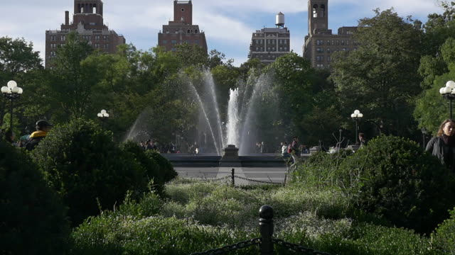 slow motion of washington square park fountain and people relaxing, new york city - 噴水点の映像素材/bロール