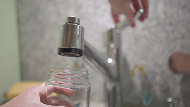 slow motion of water filling up glass from tap - one mid adult woman only stock videos & royalty-free footage