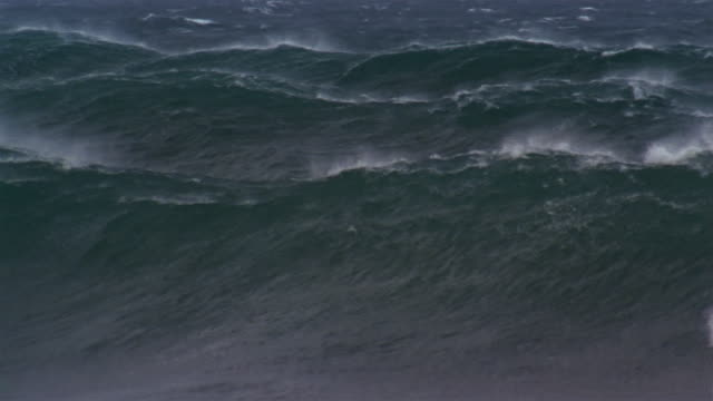 Slow motion of white caps curling toward shore and breaking on beach during storm / North Shore, Oahu, Hawaii