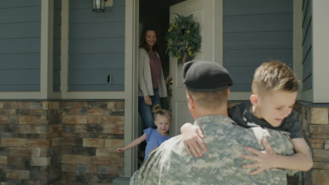 vídeos de stock e filmes b-roll de slow motion of wife and children hugging and kissing soldier returning home from duty / lehi, utah, united states - soldado exército