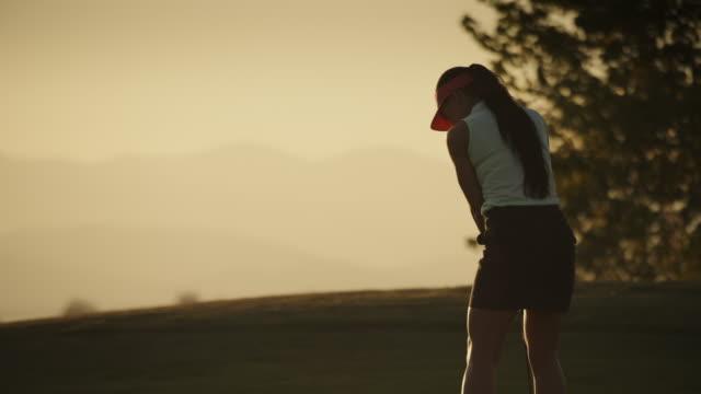 slow motion of woman celebrating while golfing at sunset / cedar hills, utah, united states - golf swing stock videos & royalty-free footage