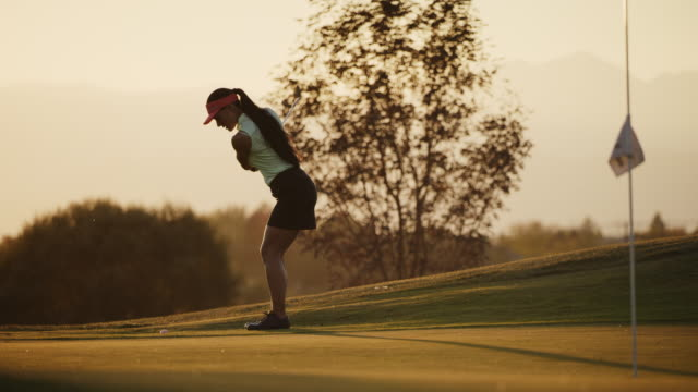 slow motion of woman chipping golf ball onto green at sunset / cedar hills, utah, united states - golf course stock videos & royalty-free footage
