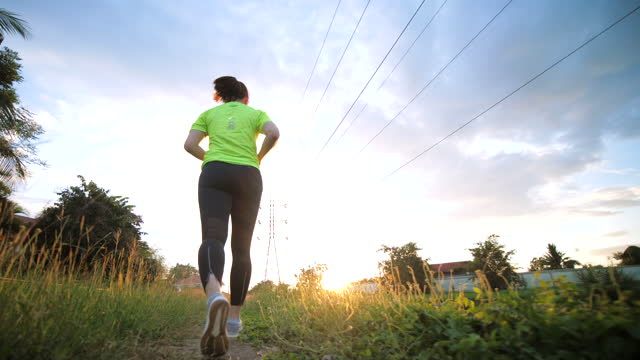 vídeos de stock e filmes b-roll de slow motion of woman exercise by running on the way in park at dusk time - triatleta