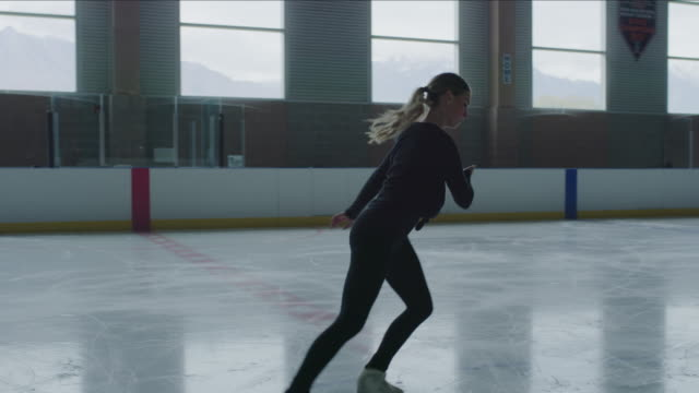 slow motion of woman figure skater skating backward on ice skating rink / murray, utah, united states - ice skating stock videos & royalty-free footage