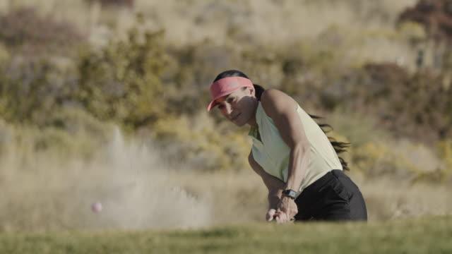 slow motion of woman hitting golf ball in sand trap / cedar hills, utah, united states - golfer stock videos & royalty-free footage