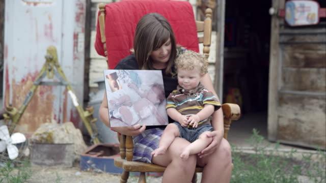 vídeos y material grabado en eventos de stock de slow motion of woman holding both child and picture of child. - en el regazo