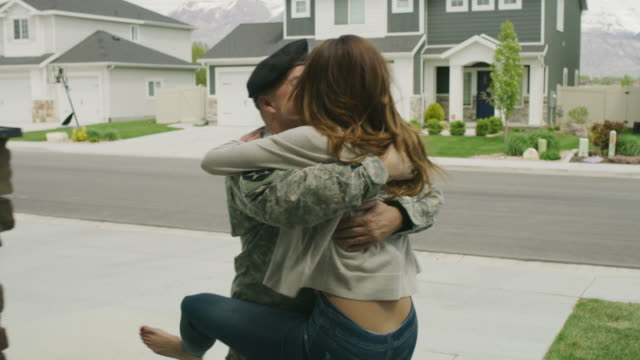 slow motion of woman hugging and kissing soldier returning home from duty / lehi, utah, united states - passione video stock e b–roll