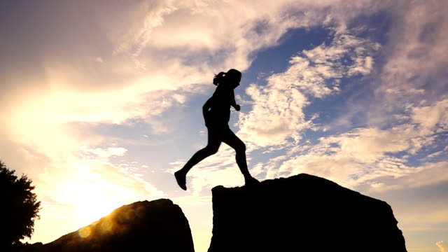 slow motion kvinna hoppa från en sten som når toppen, frihet koncept - stenstorlek bildbanksvideor och videomaterial från bakom kulisserna