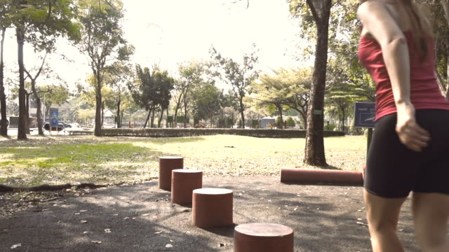 slow motion of woman jumping on the red block shape in public park - realisticfilm stock videos and b-roll footage