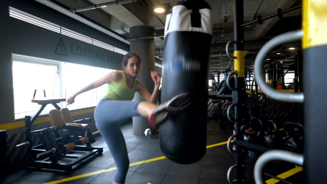 Slow motion of woman kickboxing a boxing bag at the gym