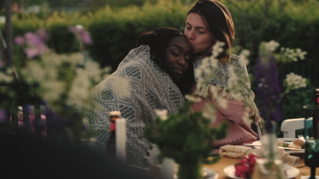 Slow motion of woman kissing partner on forehead while wearing blanket during garden party