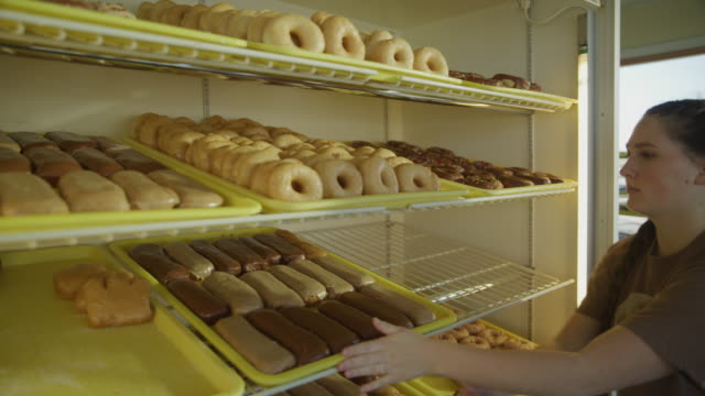 slow motion of woman placing trays of donuts on display cabinet shelf / pleasant grove, utah, united states - display cabinet stock videos & royalty-free footage