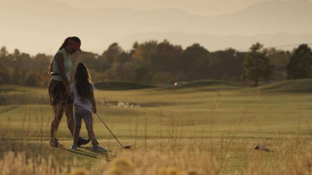 vídeos y material grabado en eventos de stock de slow motion of woman positioning girl teeing off on golf course / cedar hills, utah, united states - green de golf