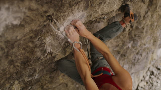 slow motion of woman rock climbing in cave near carabiner / american fork canyon, utah, united states - avventura video stock e b–roll