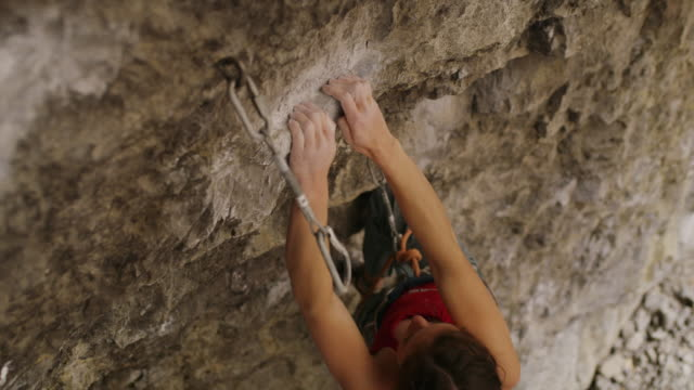 Slow motion of woman rock climbing in cave switching rope to carabiner / American Fork Canyon, Utah, United States