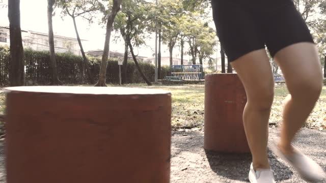 公共の公園で赤い材木の周り実行している女性のスローモーション - ランニングショートパンツ点の映像素材/bロール