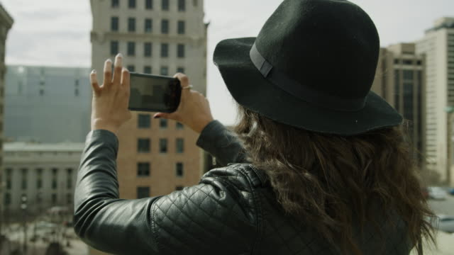 Slow motion of woman taking panoramic photograph of city with cell phone on roof / Salt Lake City, Utah, United States