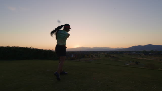 slow motion of woman teeing off on golf course at sunset / cedar hills, utah, united states - tee off stock videos & royalty-free footage