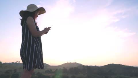 slow-motion frau mit smartphone auf hügel bei sonnenuntergang - hüfte stock-videos und b-roll-filmmaterial