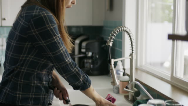 vídeos y material grabado en eventos de stock de slow motion of woman washing pan talking on cell phone and dropping it into sink / alpine, utah, united states - portability
