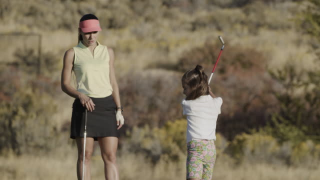 slow motion of woman watching girl golfing then high-fiving her / cedar hills, utah, united states - daughter stock videos & royalty-free footage