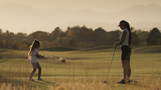 slow motion of woman watching girl teeing off on golf course then high-fiving / cedar hills, utah, united states - golf swing stock videos & royalty-free footage