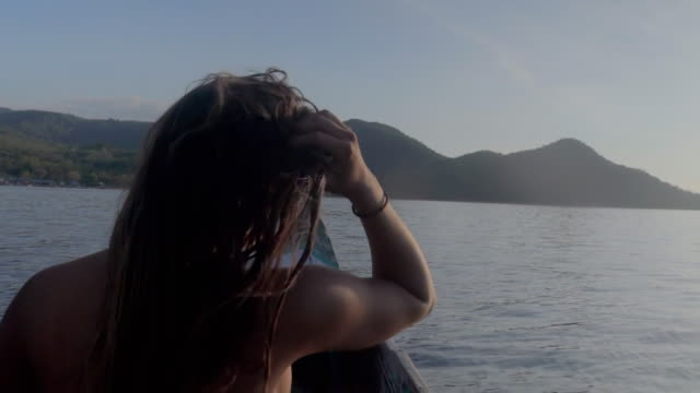 slow motion of woman with hand in hair sitting on boat over sea, she is enjoying beautiful view of mountain - lombok, bali - hand in hair stock videos & royalty-free footage