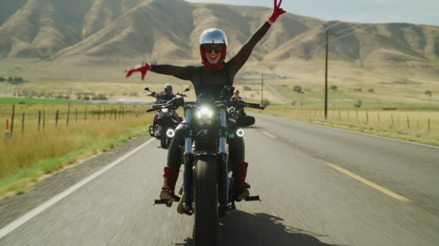 slow motion of women riding motorcycles on remote road with arms raised / payson, utah, united states - sonnenbrille stock-videos und b-roll-filmmaterial