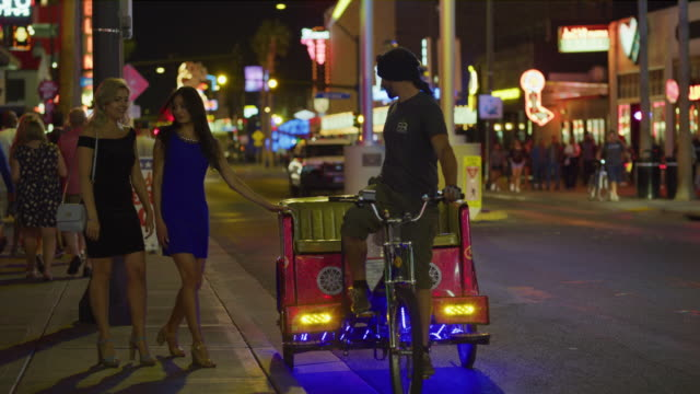 vídeos de stock, filmes e b-roll de slow motion of women waiting on sidewalk then riding in pedicab in city at night / las vegas, nevada, united states - jinriquixá puxado por bicicleta
