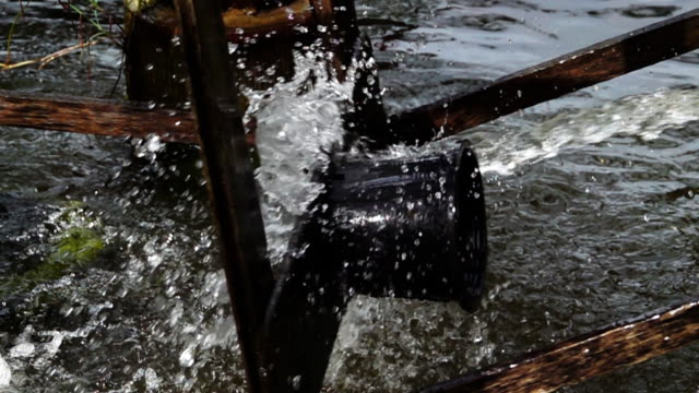 slow motion of wooden water turbine in the river. - mill stock videos and b-roll footage