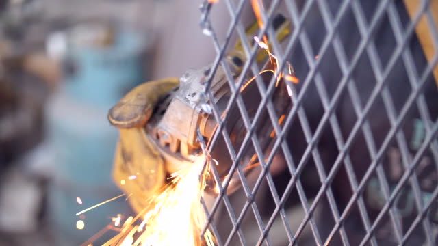 slow motion of worker using machine cutting net metal with sparking - gripping stock videos & royalty-free footage