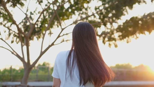 vídeos de stock e filmes b-roll de slow motion of young asian woman standing and relaxing at park, asia girl in sunset nature - cabelo humano