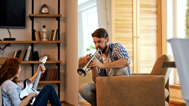 slow motion of young couple playing musical instruments at home and giving high-five to each other. - trumpet stock videos and b-roll footage