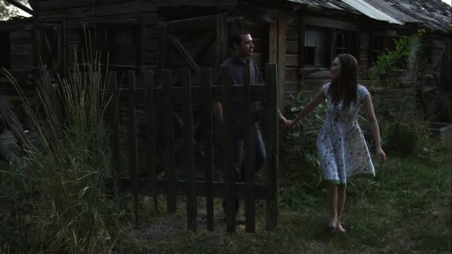 slow motion of young couple walking through gate. - オレム点の映像素材/bロール