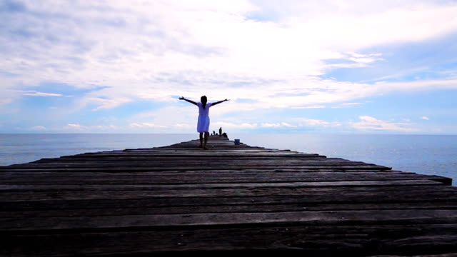 slow motion of young girls walking on wooden pier - molo video stock e b–roll