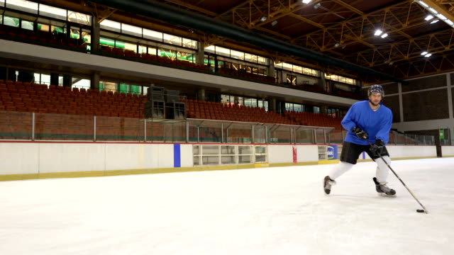 Slow motion of young ice hockey player scoring a goal on sports training in ice hockey rink.