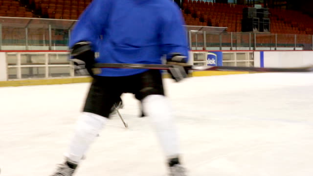 Slow motion of young ice hockey players having a match at hockey arena.