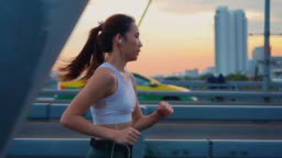 Slow motion of Young woman jogging across the bridge,Sunset