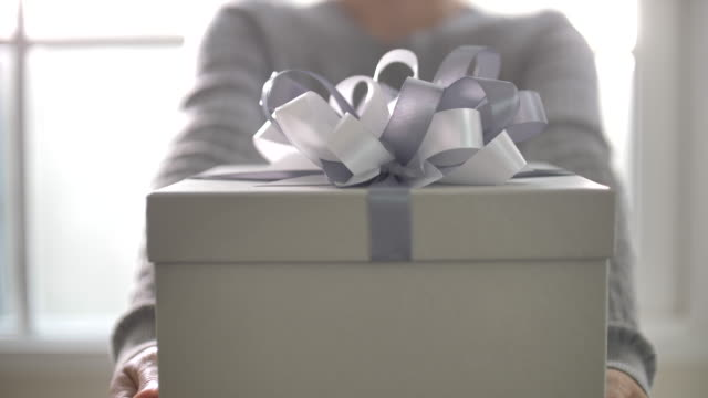 slow motion of young woman show hands holding white gift box with ribbon - congratulating stock videos and b-roll footage