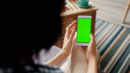 Slow motion of young woman touching smartphone with green screen at home
