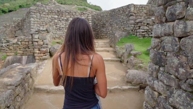 slow motion of young woman walking amidst historic peruvian old ruins - machu picchu, peru - machu picchu stock videos & royalty-free footage