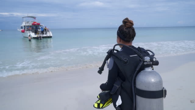 vídeos y material grabado en eventos de stock de slow motion of young woman with aqualung walking towards boat, tourists at beach against sky - montego bay, jamaica - aqualung diving equipment