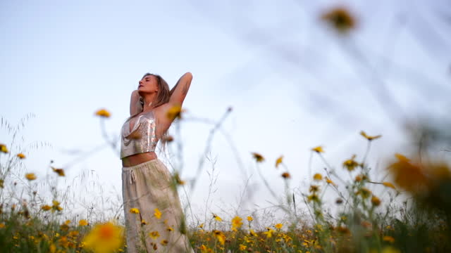 vídeos de stock e filmes b-roll de slow motion of young woman with arms outstretched in rural field, dancing against clear sky on sunny day - negev, israel - braços abertos