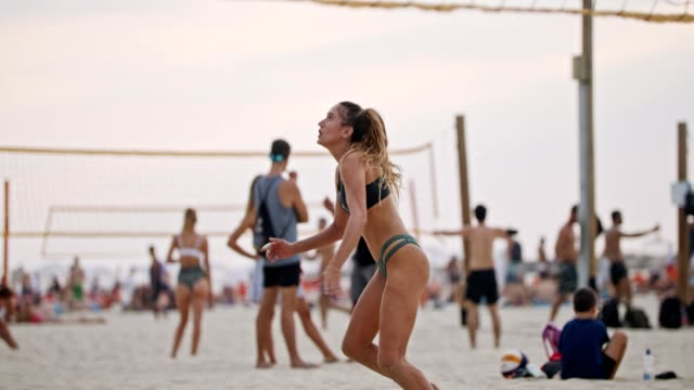 Slow motion of young women playing beach volleyball during sunset