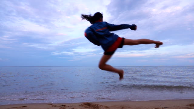 slow motion of young women practising martial arts outdoors on the beach. - curiosity stock videos and b-roll footage