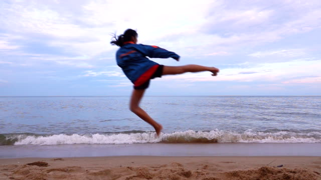slow motion of young women practising martial arts outdoors on the beach. - taekwondo stock videos & royalty-free footage