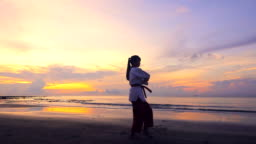 Slow motion of Young women Practising Martial Arts Outdoors On the beach at Sunset time