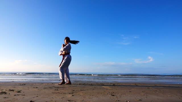 vidéos et rushes de ralenti de la jeune femme pratiquant les arts martiaux à l'extérieur sur la plage. - karaté