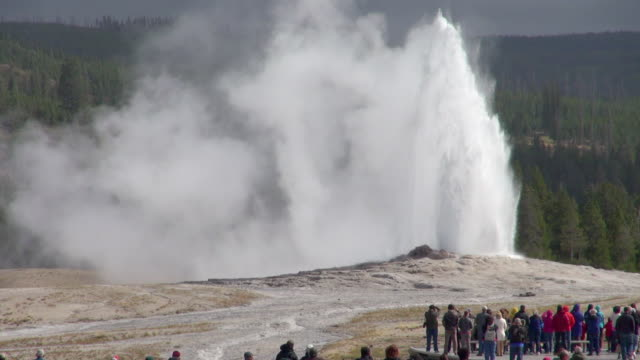stockvideo's en b-roll-footage met slow motion: old faithful with tourists in foreground - yellowstone national park