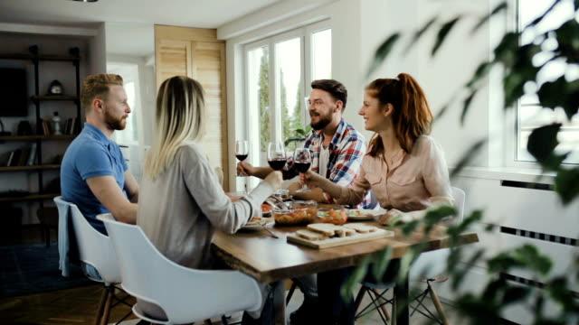 Zeitlupe auf glückliche Jugendliche Toasten mit Wein während des Mittagessens.